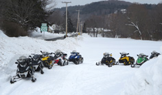 Snowmobiles parked outside firehouse during Fundraiser dinner.